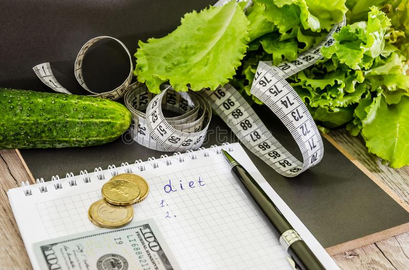 """L'iscrizione """"dieta """"su un taccuino, sui dollari, sulle monete e sulle verdure sulla tavola immagine stock libera da diritti"""