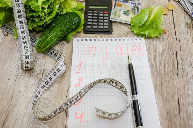 """L'iscrizione """"dieta """"su un taccuino, sui dollari, sulle monete e sulle verdure sulla tavola fotografia stock libera da diritti"""