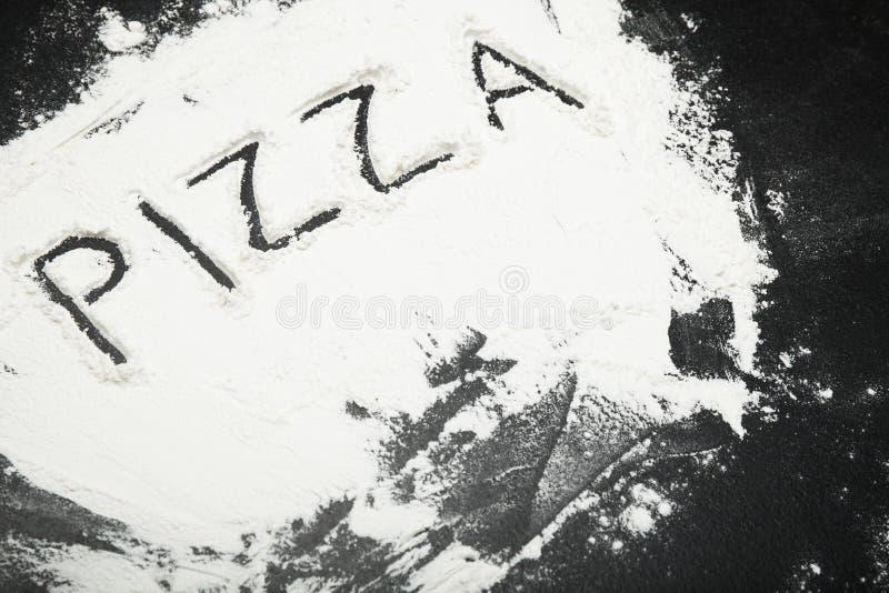 """L'iscrizione """"pizza """"sulla tavola con farina fotografie stock"""