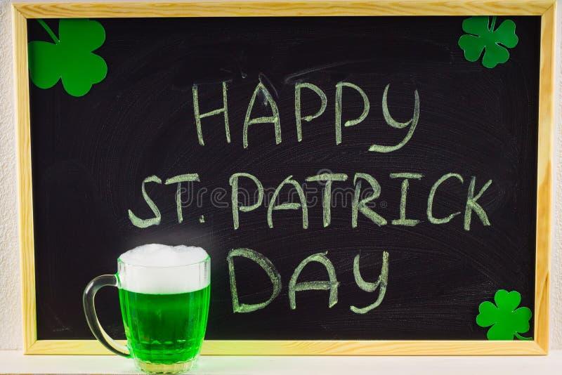 L'iscrizione con gesso verde su una lavagna: Il giorno di St Patrick felice Fogli del trifoglio bianco Una tazza con birra verde immagini stock