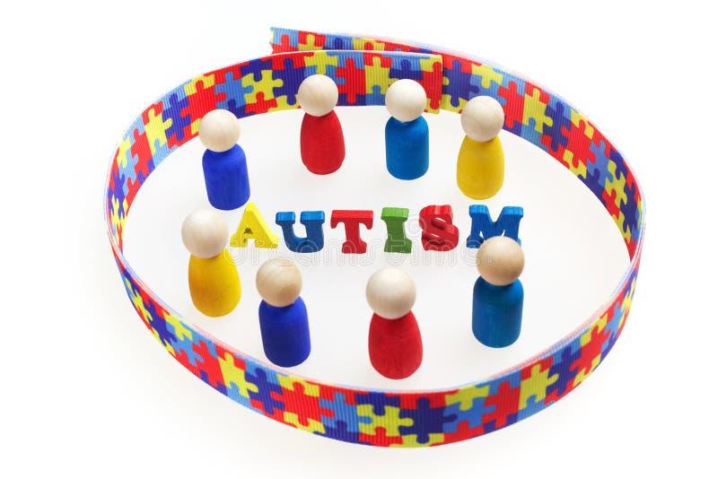 L'iscrizione di autismo con le figure ed il puzzle modellano il nastro su fondo bianco fotografie stock libere da diritti