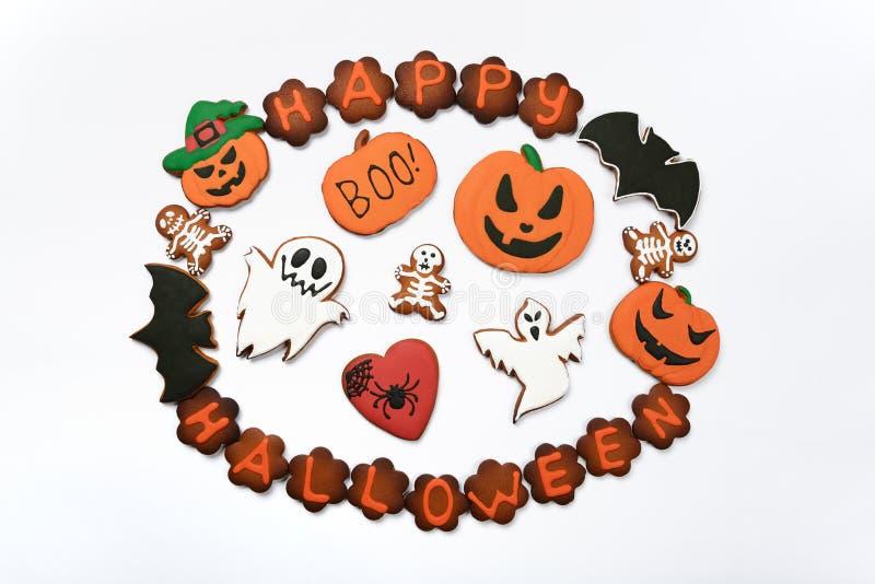 L'iscrizione, le zucche, i fantasmi e gli sceletons commestibili fatti a mano di Halloween del pan di zenzero fotografia stock