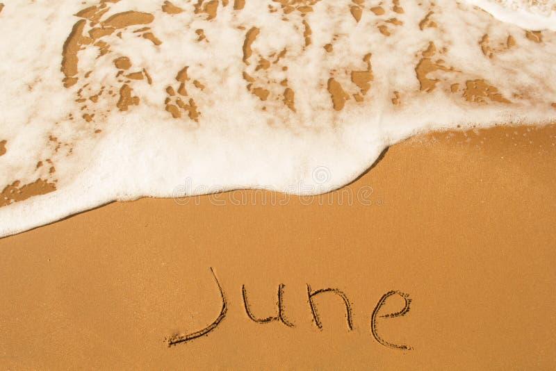 L'iscrizione sulla sabbia è giugno immagine stock