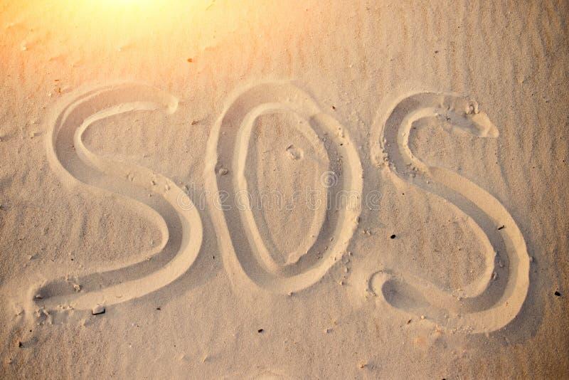 L'iscrizione sulla spiaggia di sabbia SOS fotografia stock libera da diritti