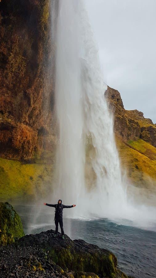 L'Islanda - condizione del giovane accanto ad una cascata potente immagine stock