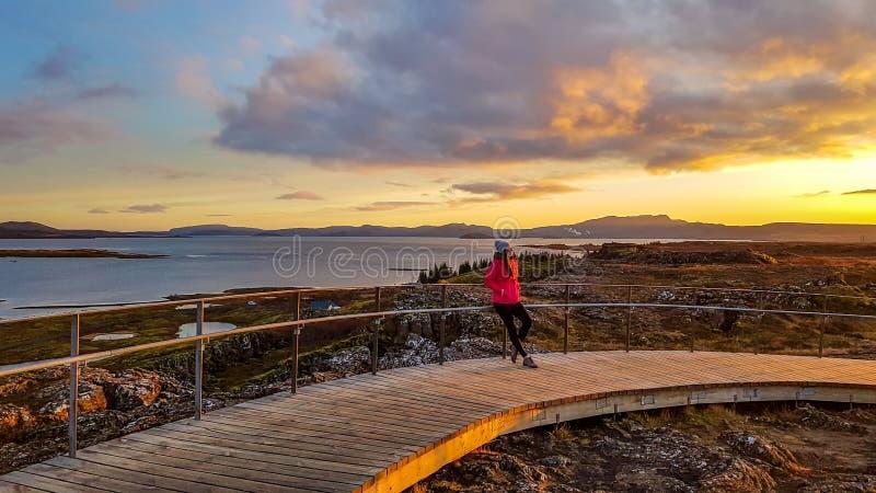 L'Islanda - condizione della ragazza alla via nel ingvellir del ½ del ¿ del ï durante il tramonto immagini stock libere da diritti