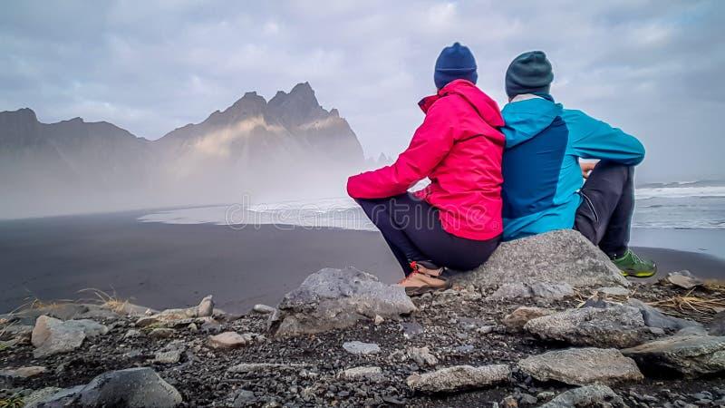 L'Islanda - coppia che si siede alla roccia, esaminante le montagne immagine stock