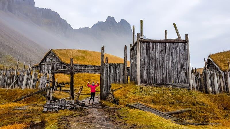 L'Islanda - una condizione della ragazza all'entrata ad un villaggio dei vikngs, situato sotto le montagne alte immagine stock libera da diritti
