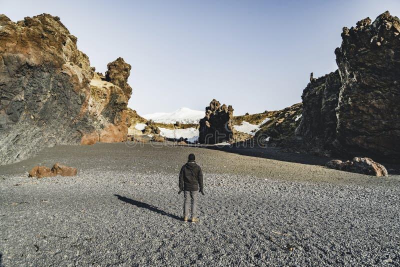 L'Islande noircissent le voyageur de touristes de jeune homme de sable de plage avec le ciel bleu de neige de montagne de snaefel photographie stock