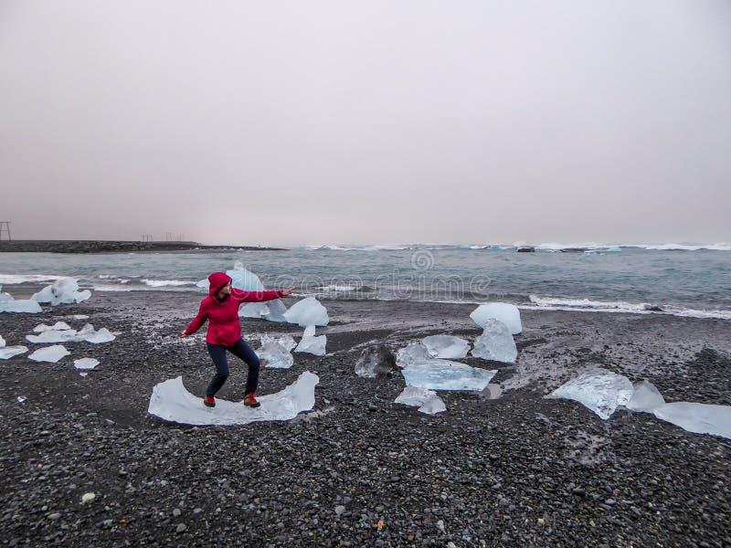 L'Islande - une fille feignant pour surfer ? l'iceberg de glace sur la plage noire de sable photographie stock
