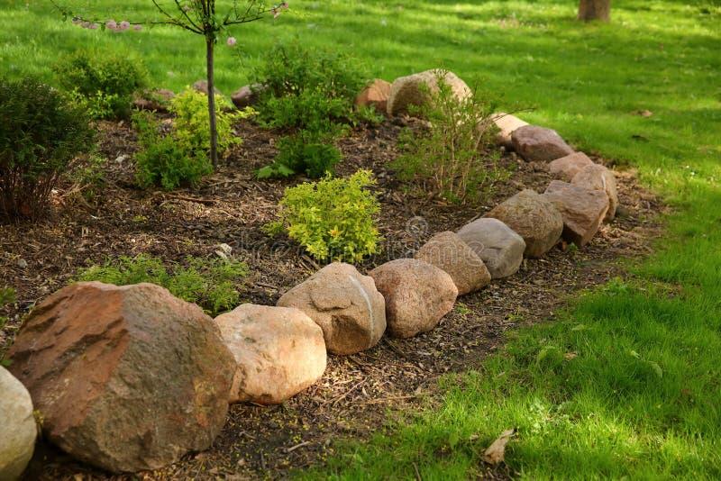 L'isola del giardino sul prato inglese è stata coperta di grandi massi e le piante ornamentali sono state piantate dentro  immagini stock