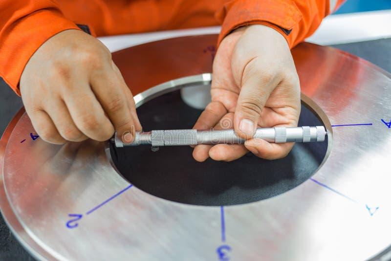 L'ispettore sta ispezionando sul piatto di orifizio per controllare il diametro fotografia stock
