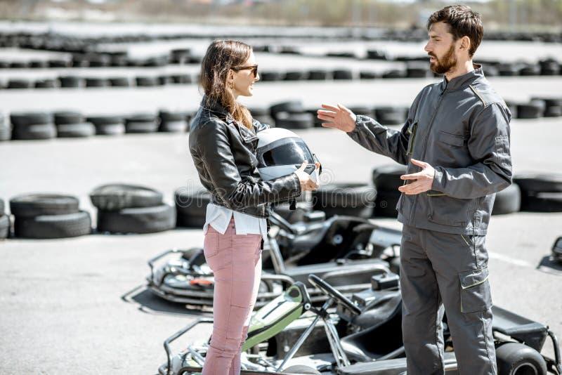 L'istruttore con la donna sulla pista con va-karts immagini stock