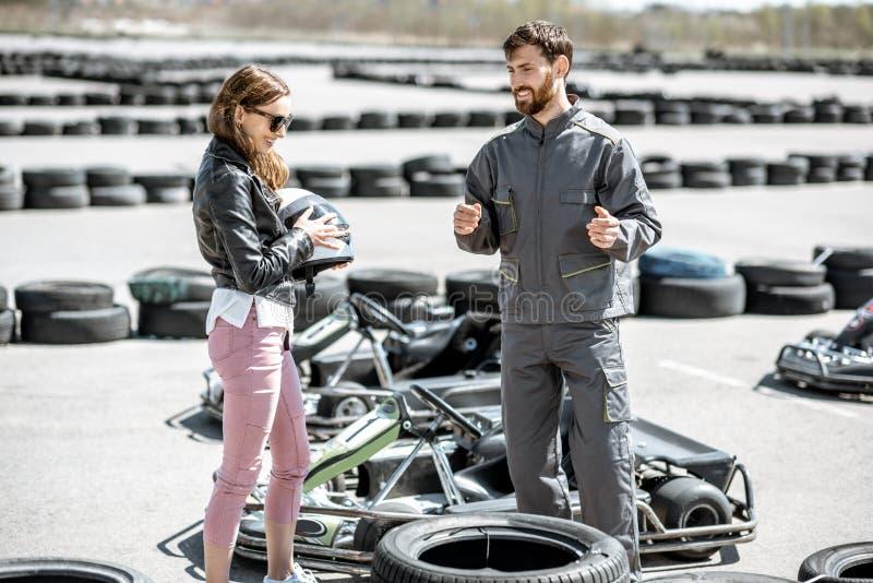 L'istruttore con la donna sulla pista con va-karts immagini stock libere da diritti