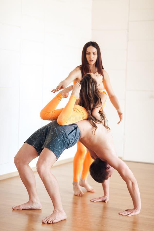 L'istruttore insegna ad una poca ragazza di yoga, mostra una posa stretta dentro fotografie stock libere da diritti