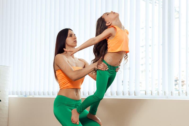 L'istruttore insegna ad una poca ragazza di yoga, mostra una posa stretta nell'yoga vicino alla finestra fotografia stock libera da diritti