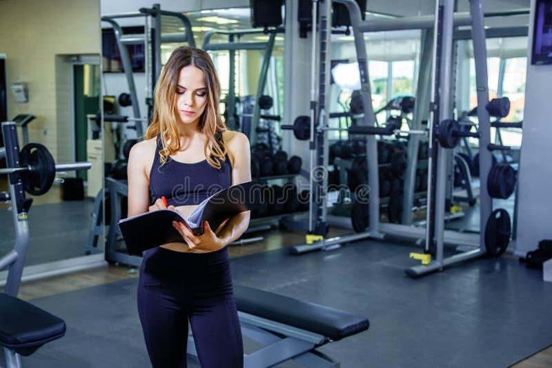 L'istruttore personale della giovane donna redige il piano di formazione in un taccuino fotografia stock