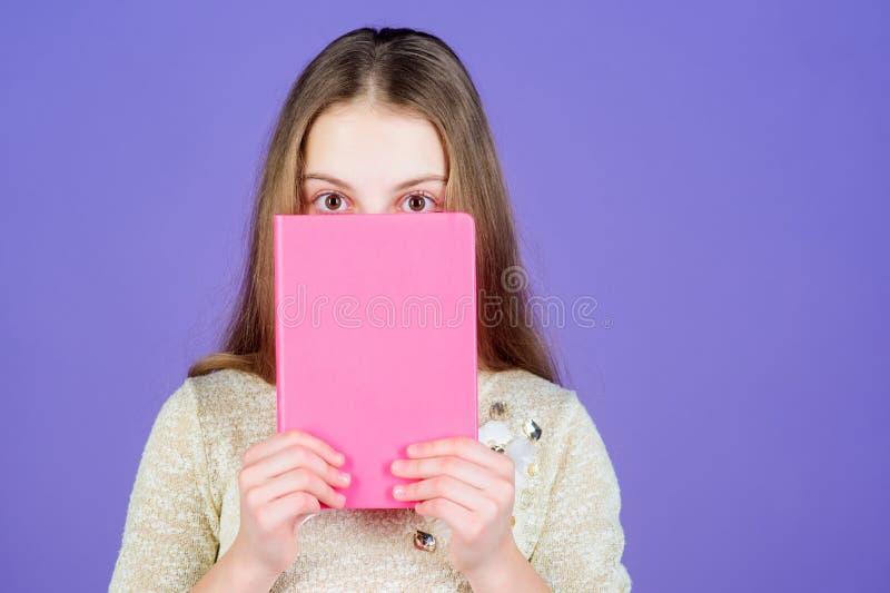 L'istruzione è circa conoscenza d'allargamento Piccolo fronte adorabile della copertura della ragazza con il libro Piccolo bambin fotografia stock