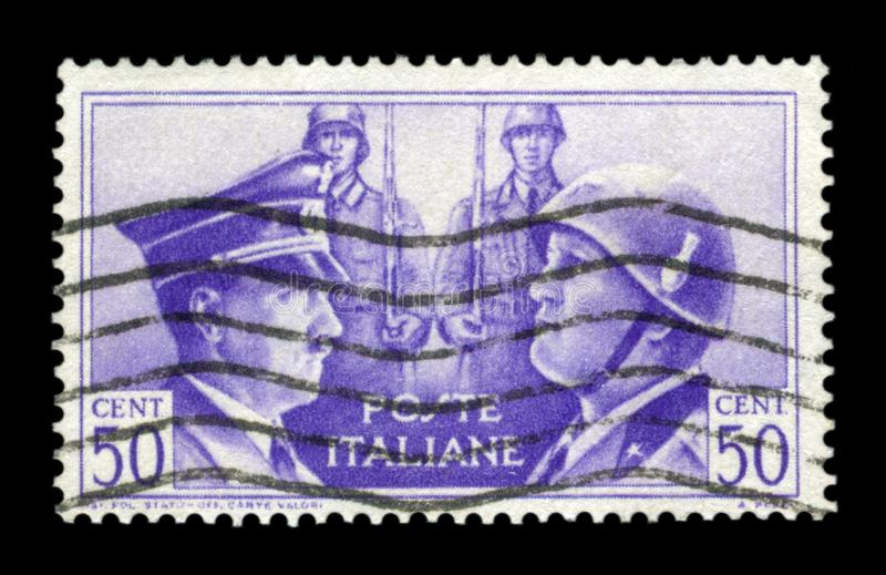L'ITALIA - CIRCA 1941: Bollo storico italiano: Fratellanza Tedesco-italiana in armi, ritratti di Hitler e Mussolini con due vendu fotografia stock libera da diritti