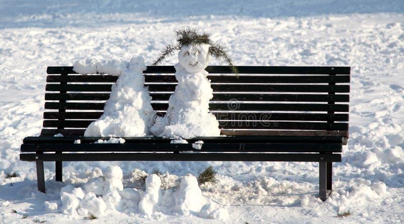 2012 l'Italie, bonhommes de neige sur un banc de parc fondent au soleil photo stock
