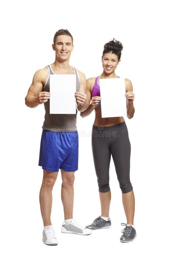L'jeune homme et la femme dans les sports équipe retenir les cartes vierges photographie stock