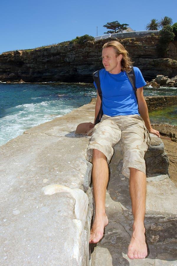L'jeune homme heureux s'assied sur la pierre photo libre de droits