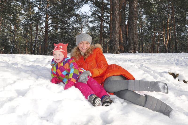 L kleines Mädchen mit ihrer Mutter, die vorn auf dem Schnee in der Kiefer liegt stockfotografie
