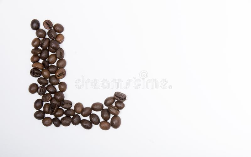 L - large letter of english alphabet. Made up of unmolished roasted coffee beans on a white background royalty free stock images