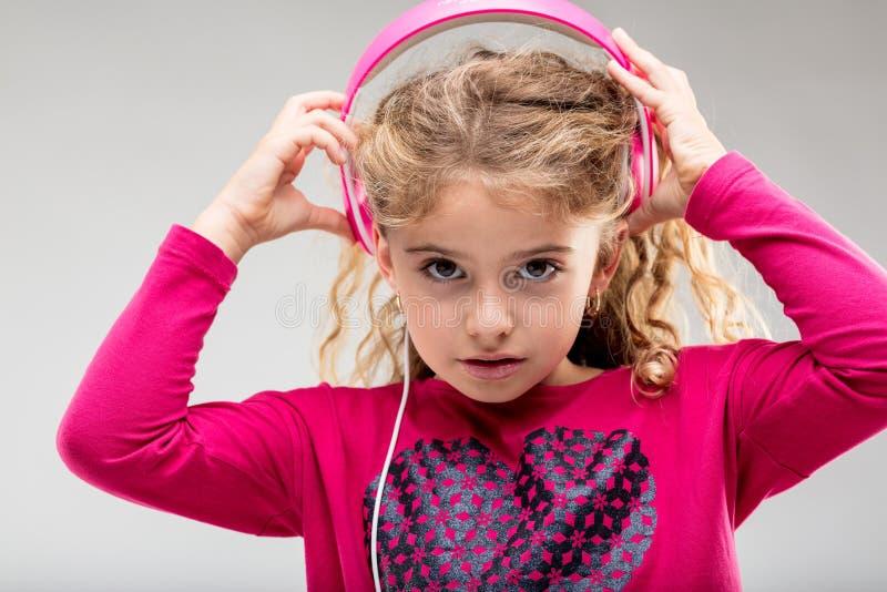 L menina que escuta a música em fones de ouvido cor-de-rosa foto de stock