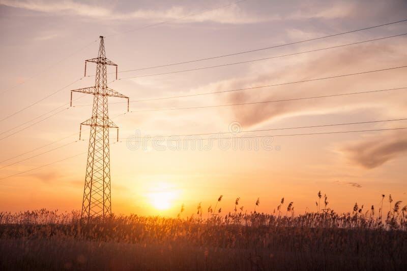 L?nea el?ctrica en la puesta del sol Torres de alto voltaje imagen de archivo