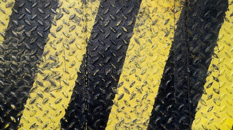 L?nea negra y amarilla pintura en fondo antideslizante del metal imagenes de archivo