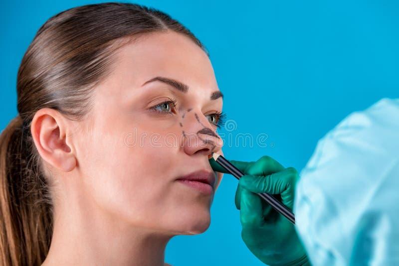 L?neas de la correcci?n del drenaje del Beautician en cara de la mujer Antes del operetion de la cirug?a pl?stica Aislado en azul fotografía de archivo