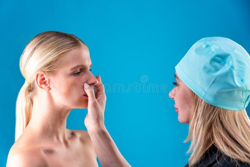 L?neas de la correcci?n del drenaje del Beautician en cara de la mujer Antes del operetion de la cirug?a pl?stica Aislado en azul imagen de archivo