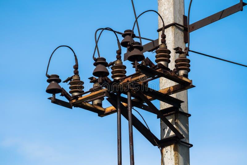 L?neas el?ctricas de alto voltaje del polo y de transmisi?n con el cielo azul claro Pilones de la electricidad en campo de la ceb foto de archivo
