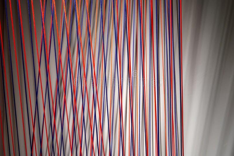 L?neas multicoloras instalaci?n de las cuerdas en interior iluminado fotografía de archivo