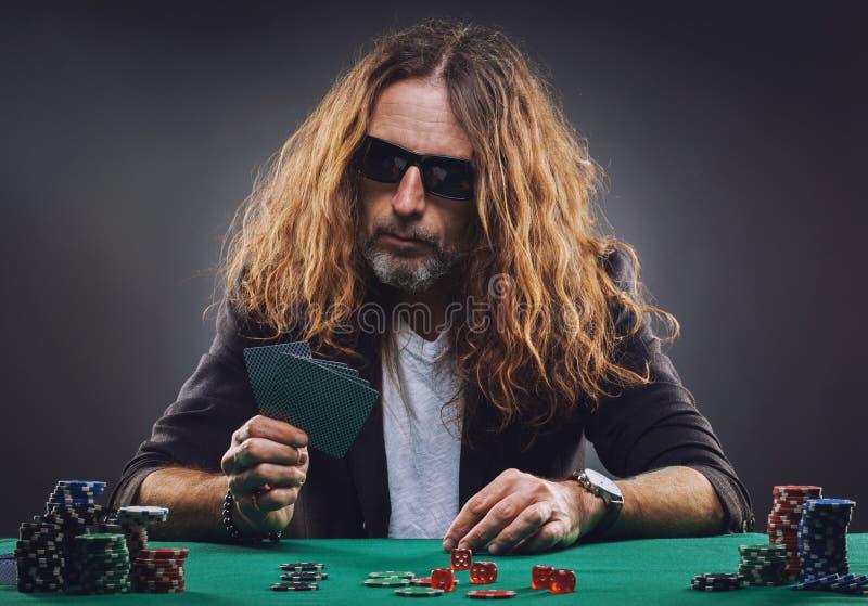 L?ngh?rig stilig man som spelar poker i en kasino arkivfoton