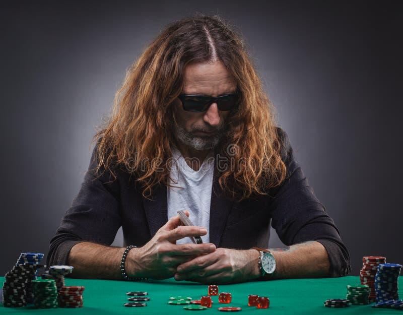 L?ngh?rig stilig man som spelar poker i en kasino royaltyfri fotografi