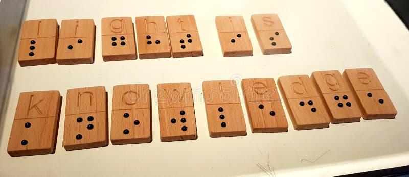 L'obscurité est ignorance, lumière est la connaissance - écrite dans l'alphabet de Braille images stock
