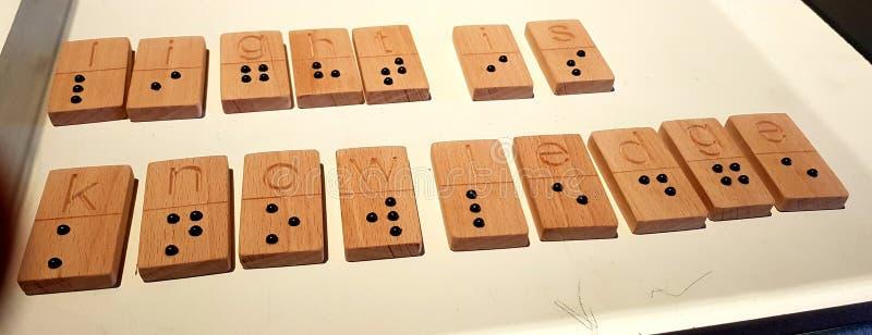 L'obscurité est ignorance, lumière est la connaissance - écrite dans l'alphabet de Braille images libres de droits
