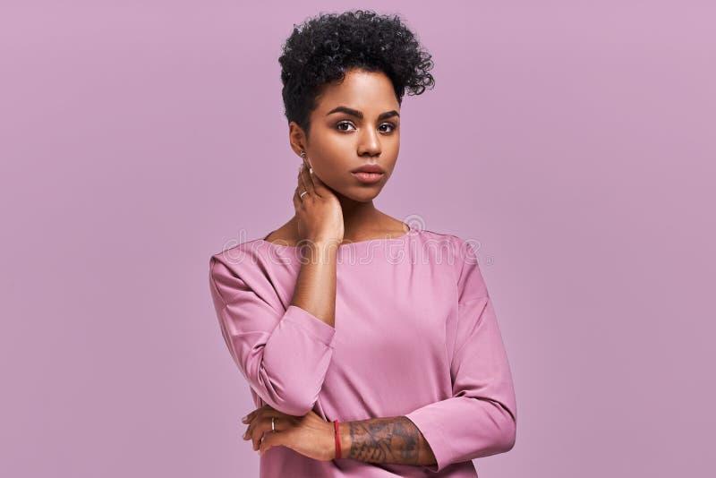 L'obscurité magnifique a pelé la jeune femelle avec la coiffure d'Afro et le regard sûr, poses pour la magazine à la mode, regard photos libres de droits