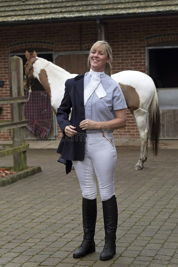 L'obtention de cavalier de cheval de femme s'est habillée dans une veste bleue photos libres de droits