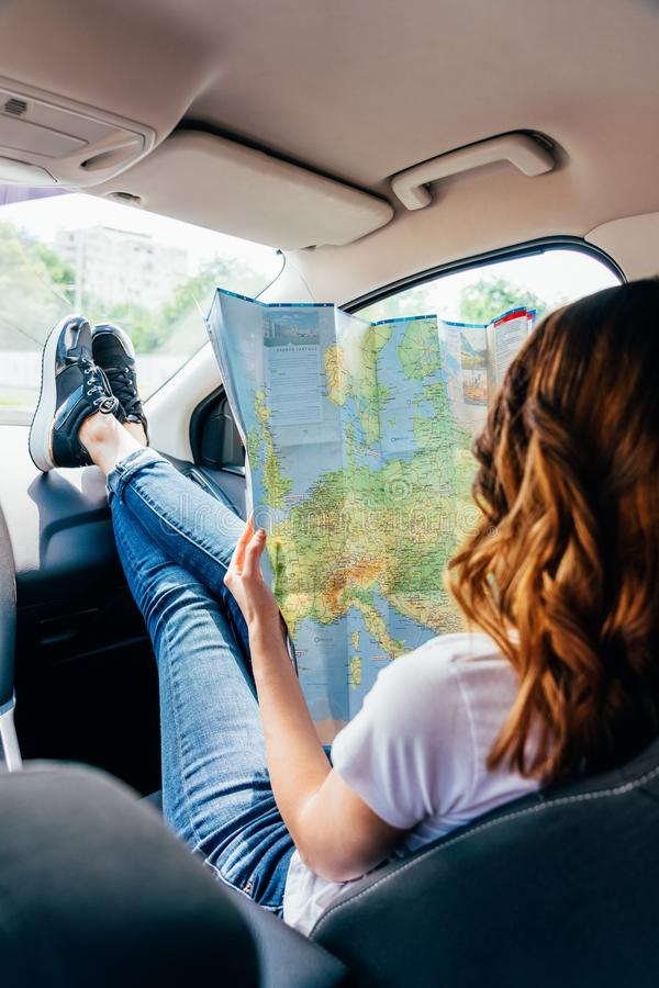 L'obtention de jeune femme préparent pour voyager par la voiture et le regard sur la carte photographie stock