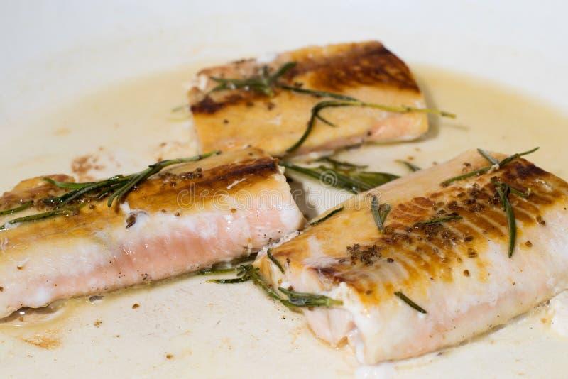 L'obtention saumonée de filets a fait cuire sur une casserole avec le romarin photo libre de droits