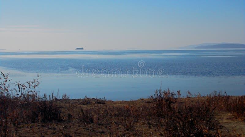 L'océan fusionne avec le ciel L'hiver Plage nue Glace bleue de la mer images stock
