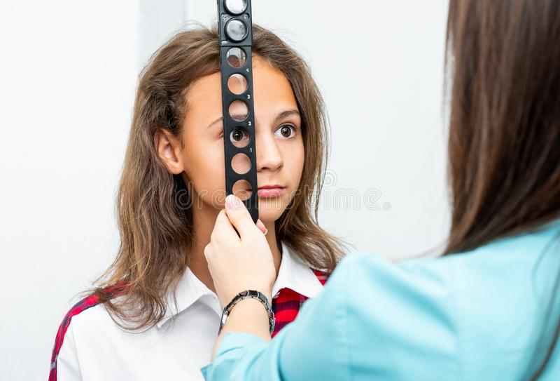 L'oculiste examine l'adolescente dans la clinique ophthalmologique image stock