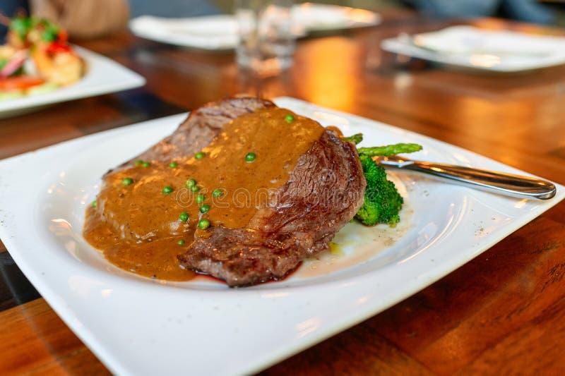 L'oeil australie de nervure de bifteck de boeuf a grillé avec rare de milieu de maturité avec de la sauce au poivre image stock