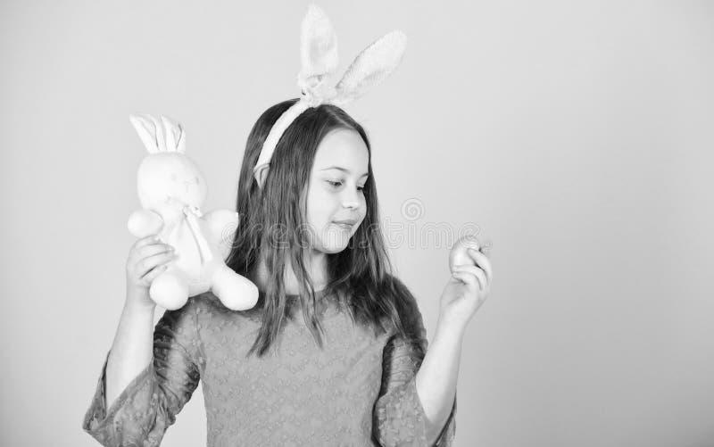 L'oeuf est un symbole d'une nouvelle vie Enfant mignon avec le lapin de Pâques apportant l'oeuf Peu fille tenant l'oeuf de pâques photographie stock