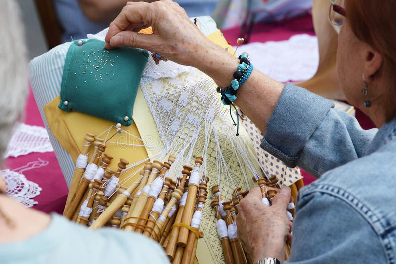 L'officina senior attiva della gente con il pizzo di bobina tradizionale lavora all'uncinetto Le mani dettagliano e svuotano lo s fotografie stock libere da diritti