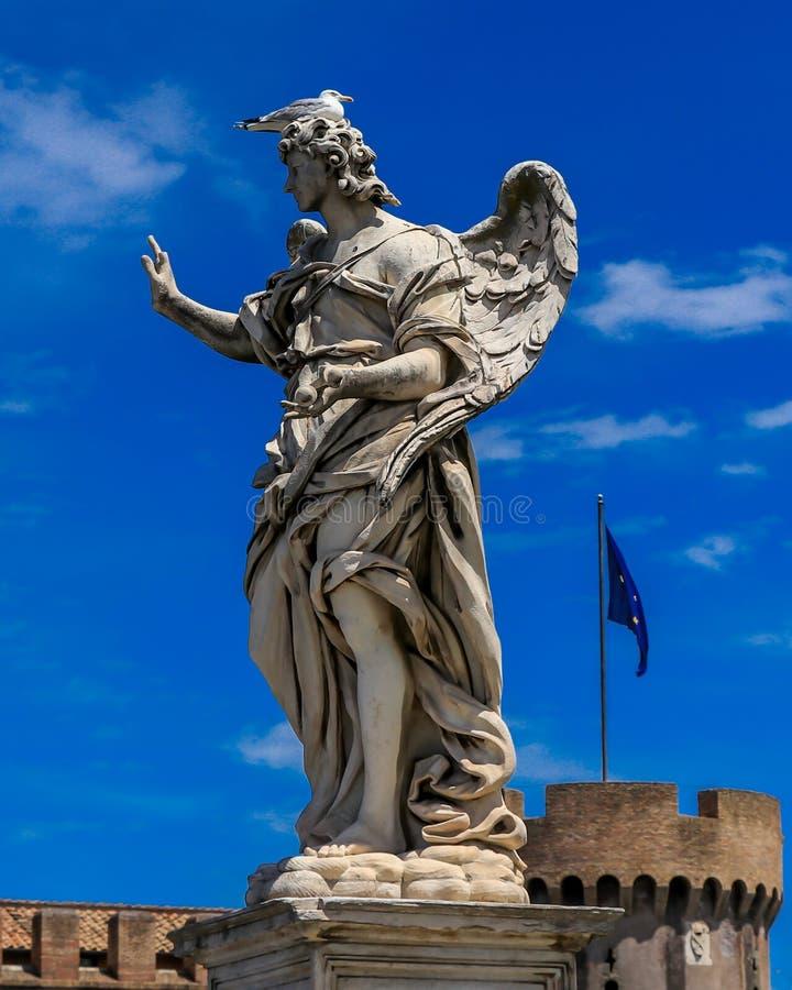 L'oiseau se repose sur la statue d'un ange, sur le fond Castel Sant Angelo et le drapeau de l'UE photo stock