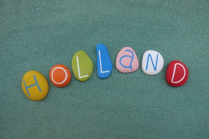 L'Olanda, ricordo composto con le multi pietre colorate del mare sopra la sabbia verde fotografia stock